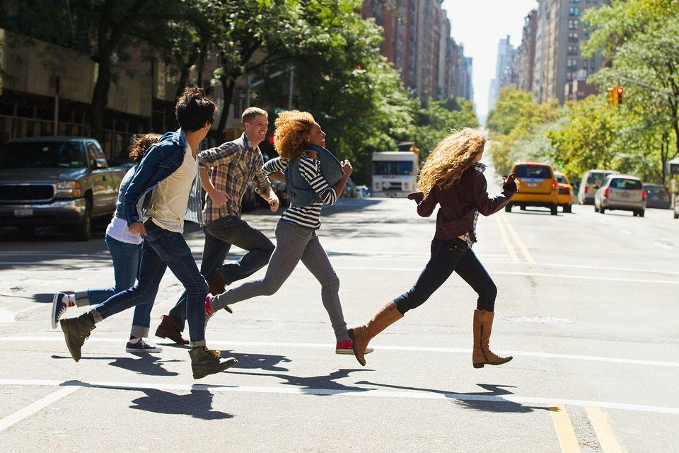 ajustes Cinco amigos corriendo por la calle de la ciudad
