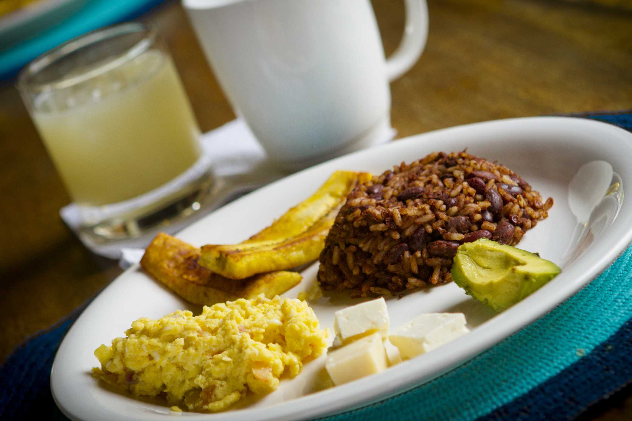 A traditional Salvadoran breakfast, with avocado eggs, beans and rice, and plantians