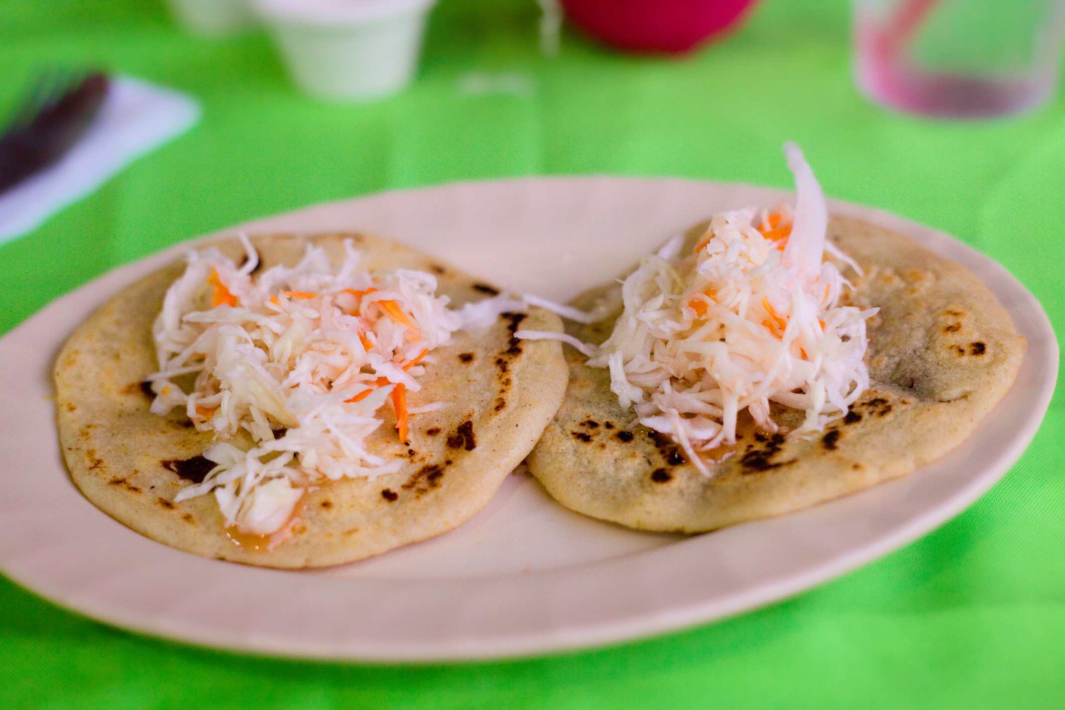 Two pupusas with cole slaw on top of them