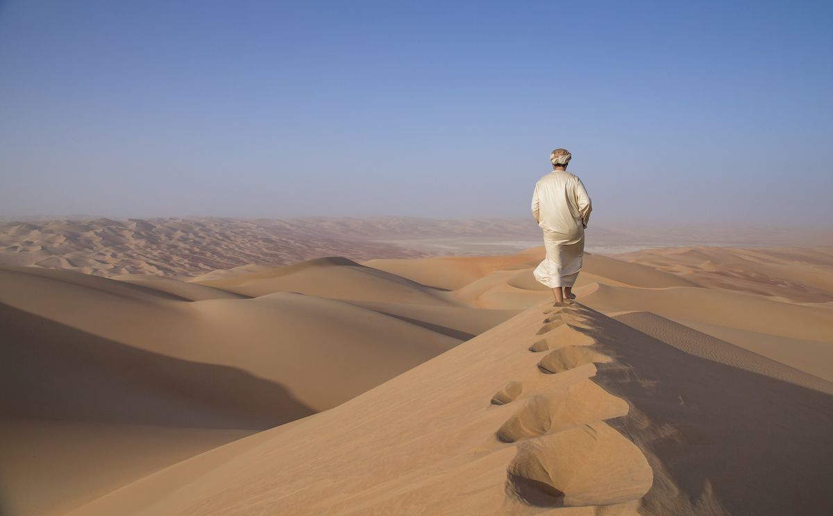 A man walks through the desert of the Empty Quarter