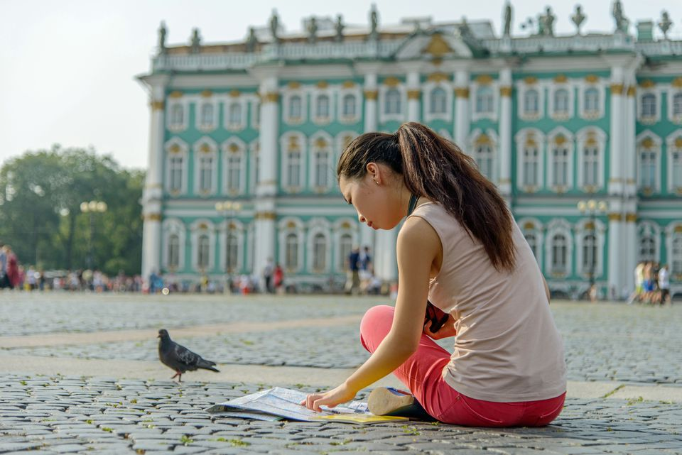 Student reading a map on a cobblestone street in front of the Hermitage, Russia
