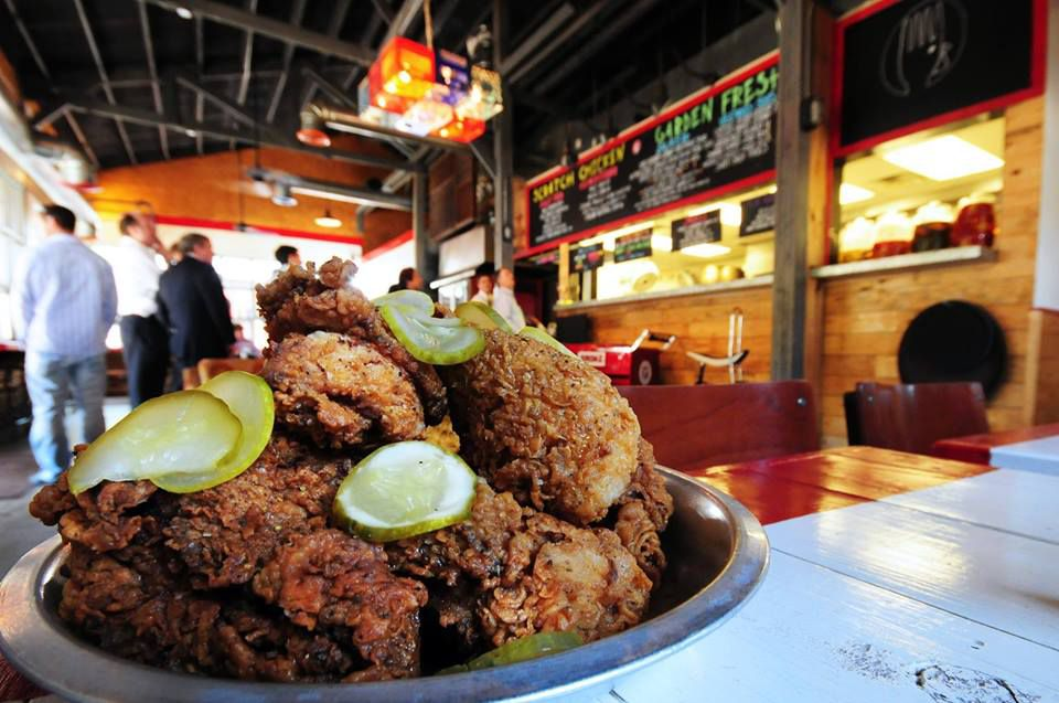 Bowl of Fried Chicken with pickle slices on a red and white table with people in line to order in the background