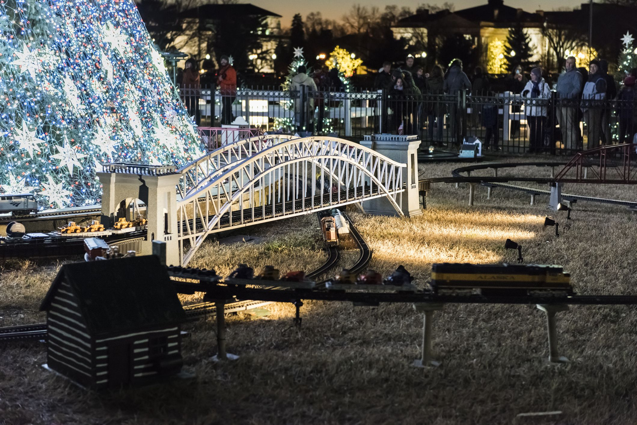 National Mall Christmas tree with visitors illuminated with toy trains