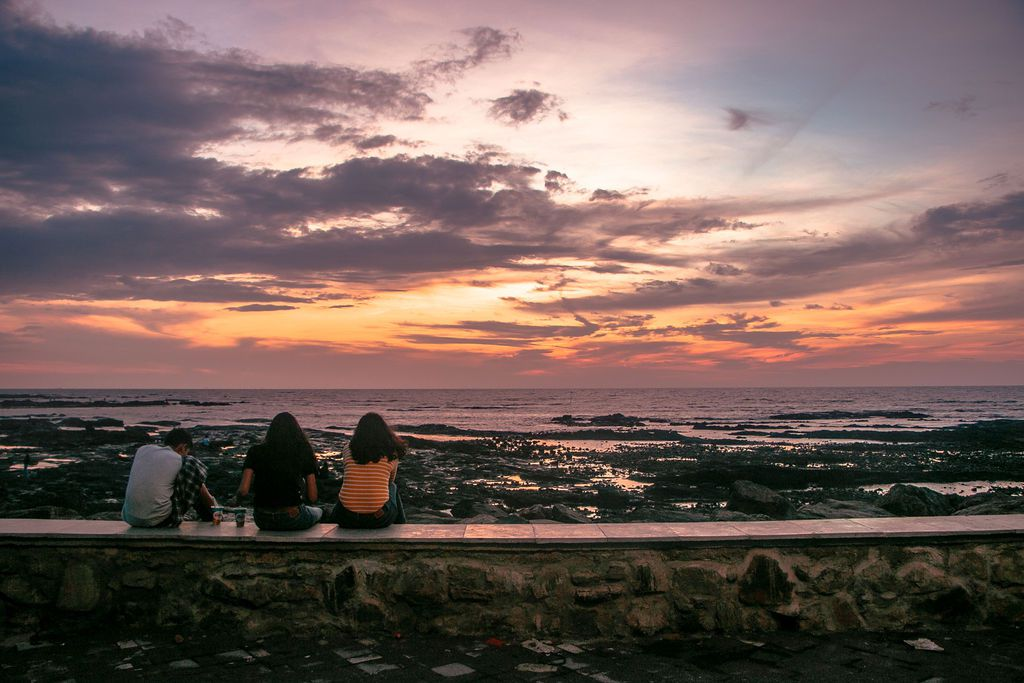 Teens sitting on the ledge at Bandstand overlooking sunset over the water