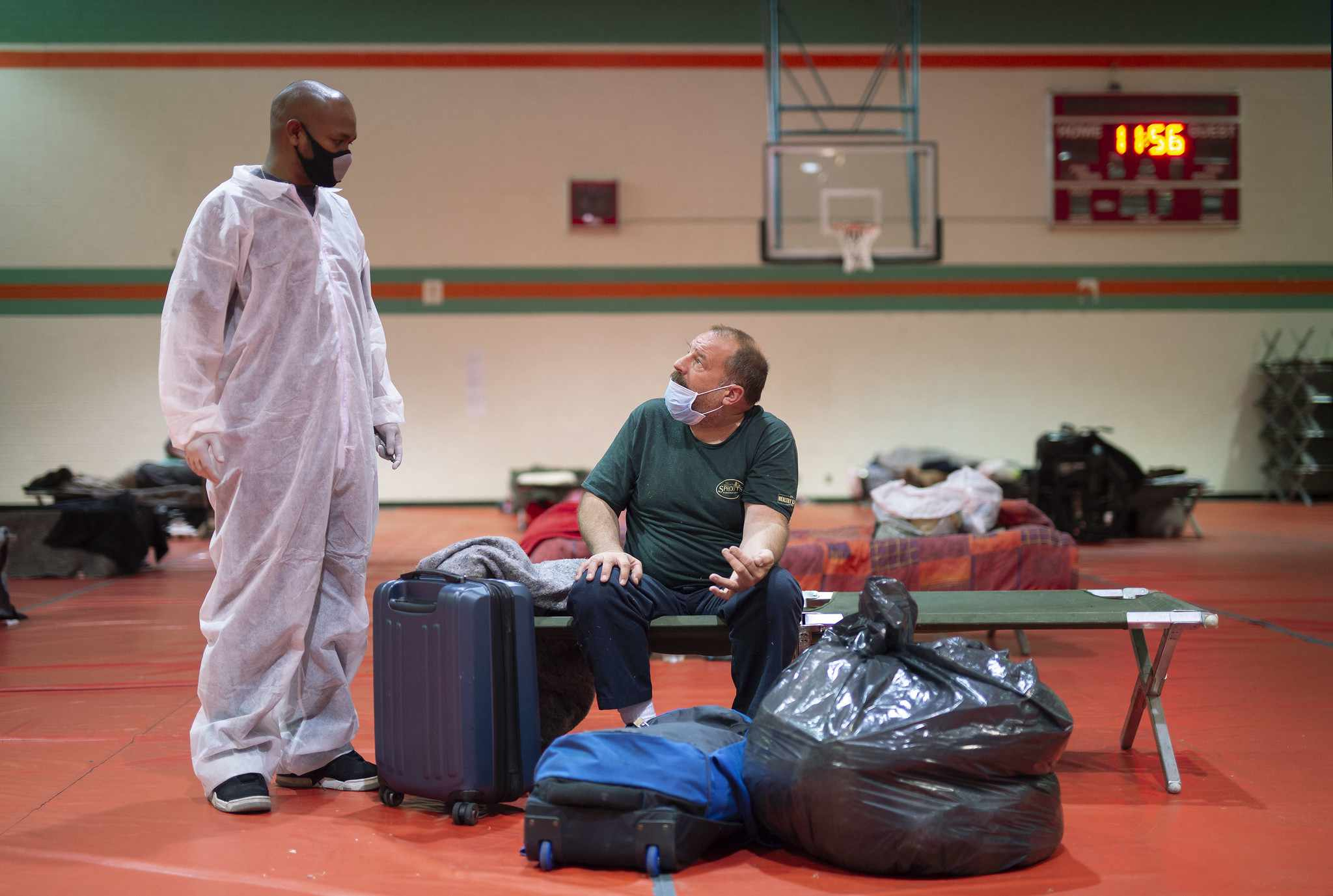 A man helps an unhoused man get to shelter