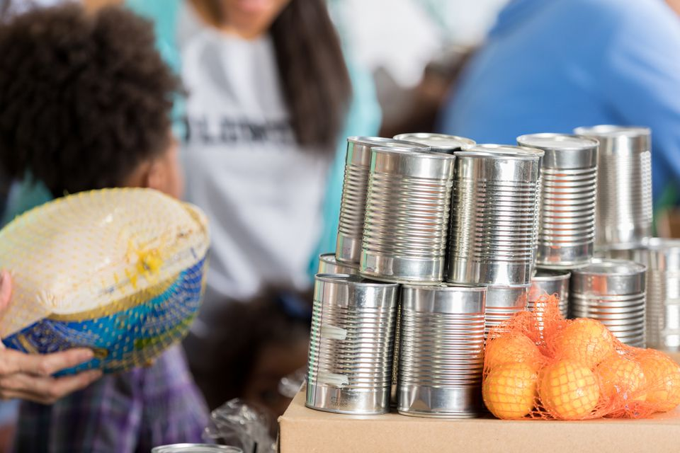 Canned food, oranges, and uncooked turkey as part of a Thanksgiving food drive.