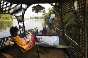 Tourist relaxes as she is punted through Keralan Backwaters near Alleppey.