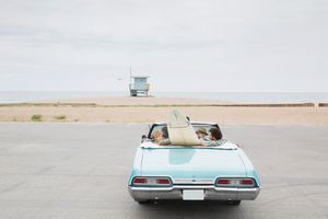 vintage convertible with surfboard arriving beach
