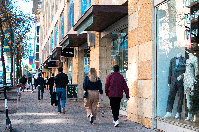 Gente caminando por la calle pasando tiendas