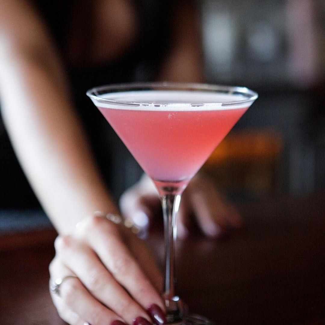 A feminine hand with dark red nail polish holding the bottom of a martini glass filled with a pink liquid
