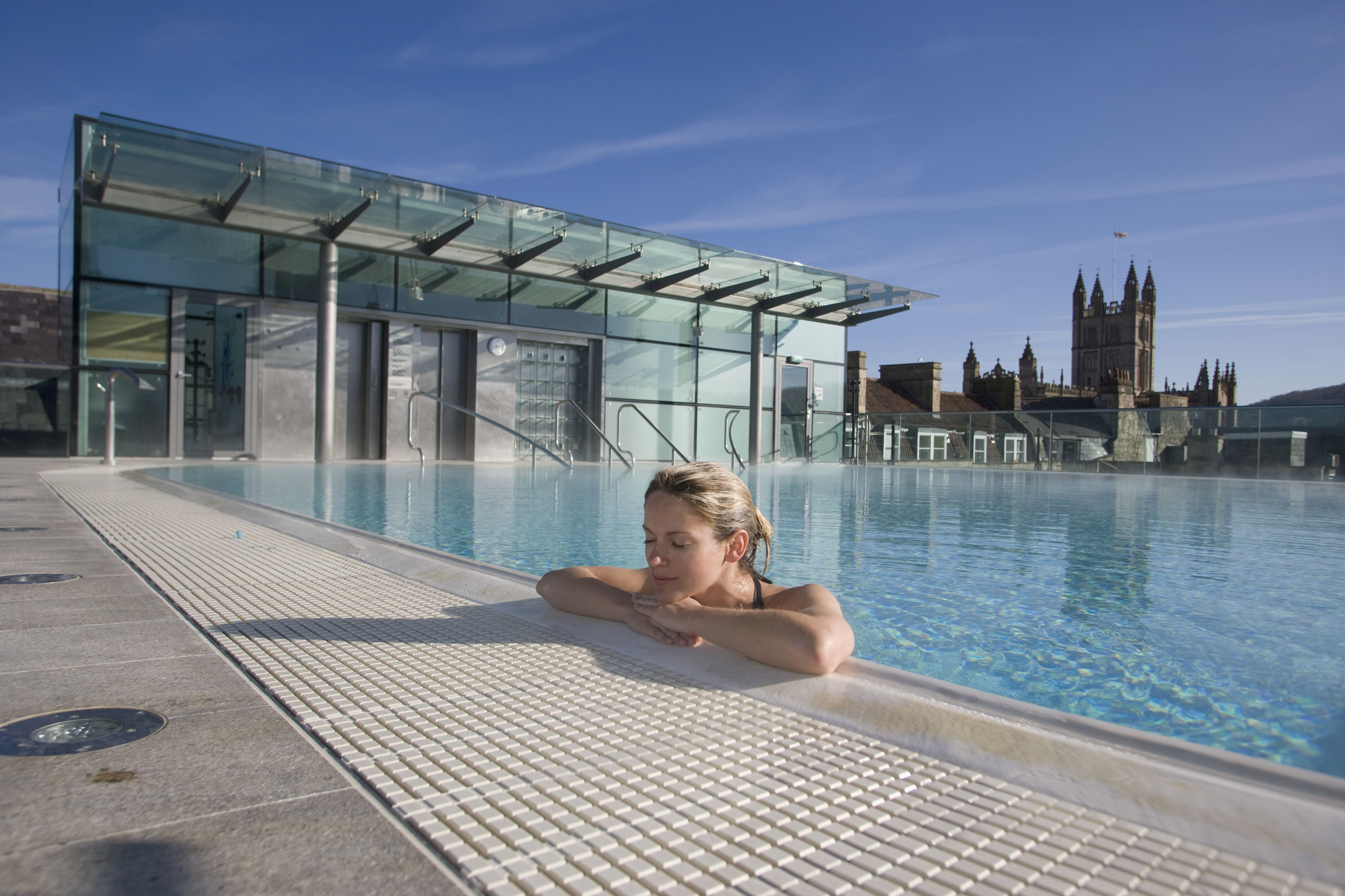 Uk, England, Bath Abbey In Background; Bath, Young Woman Relaxing In Roof Top Pool At Thermae Bath Spa