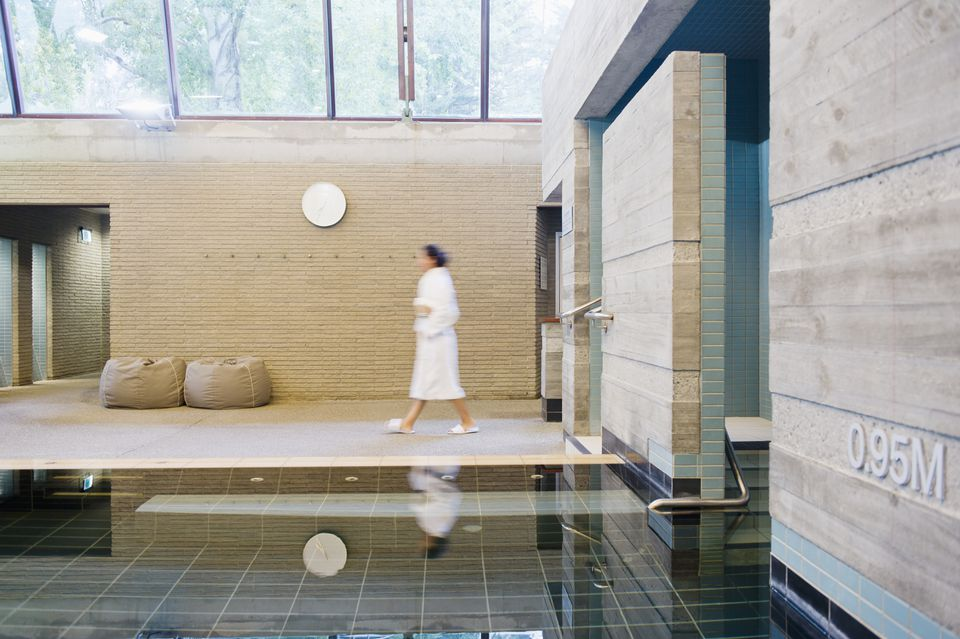 Woman in bathrobe walking in wellness spa