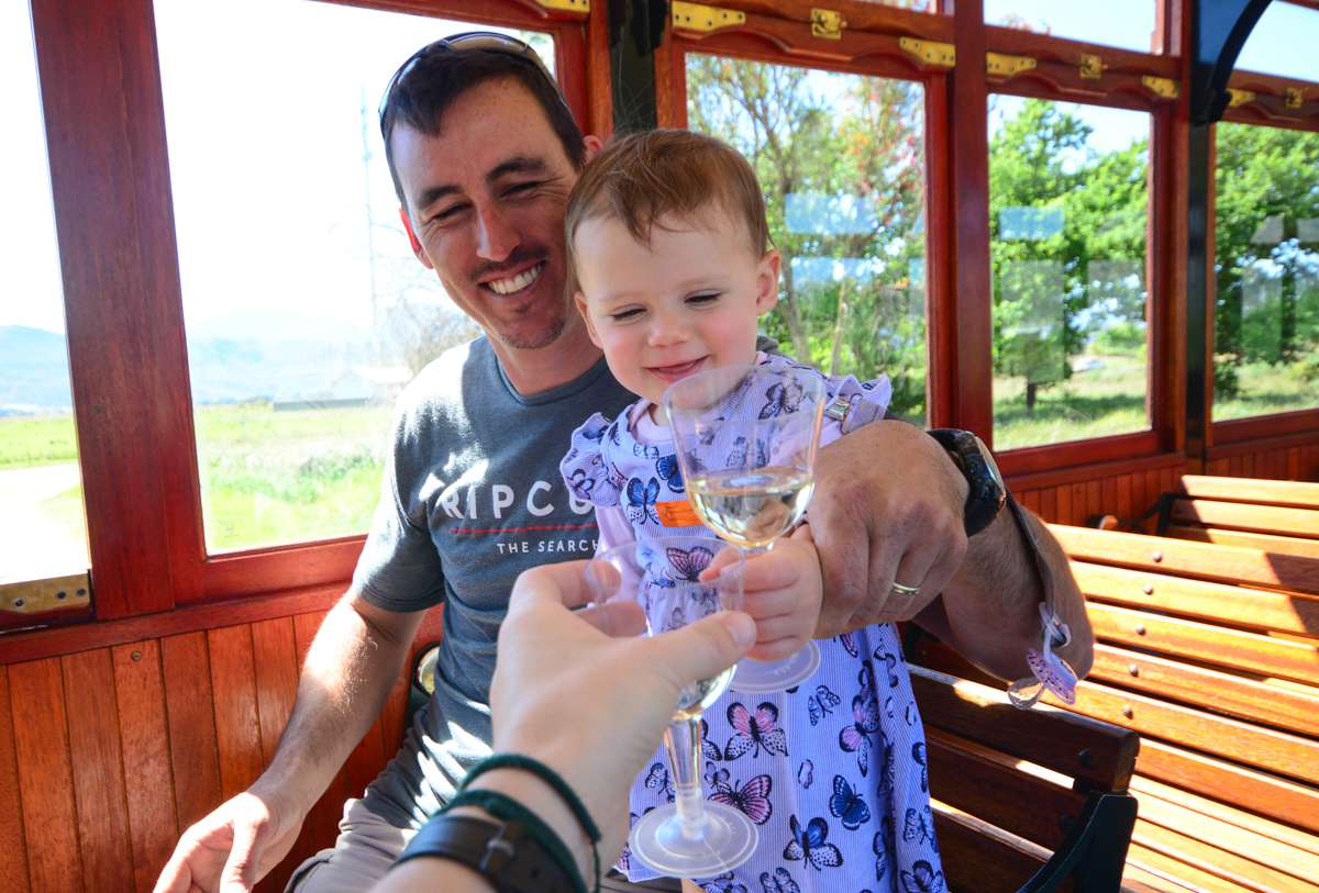 Padre e hija brindando copas en el Tranvía del Vino Franschhoek