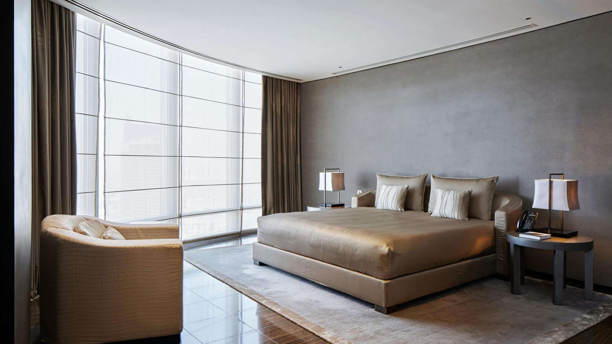 Minimalist gray and gold hotel room with queen size bed, arm chair, and large windows