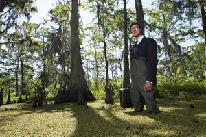 Businessman standing in swamp with briefcase