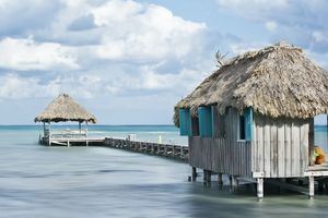 an over-the-ocean dock sits on blue water in Belize