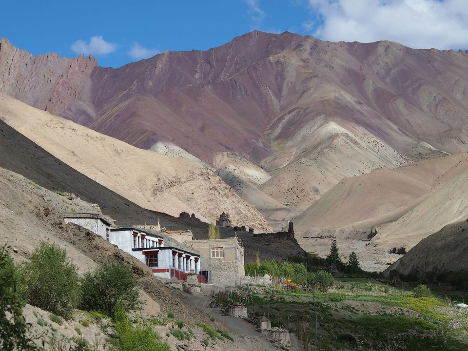 brown and pink mountains with a white building and grass