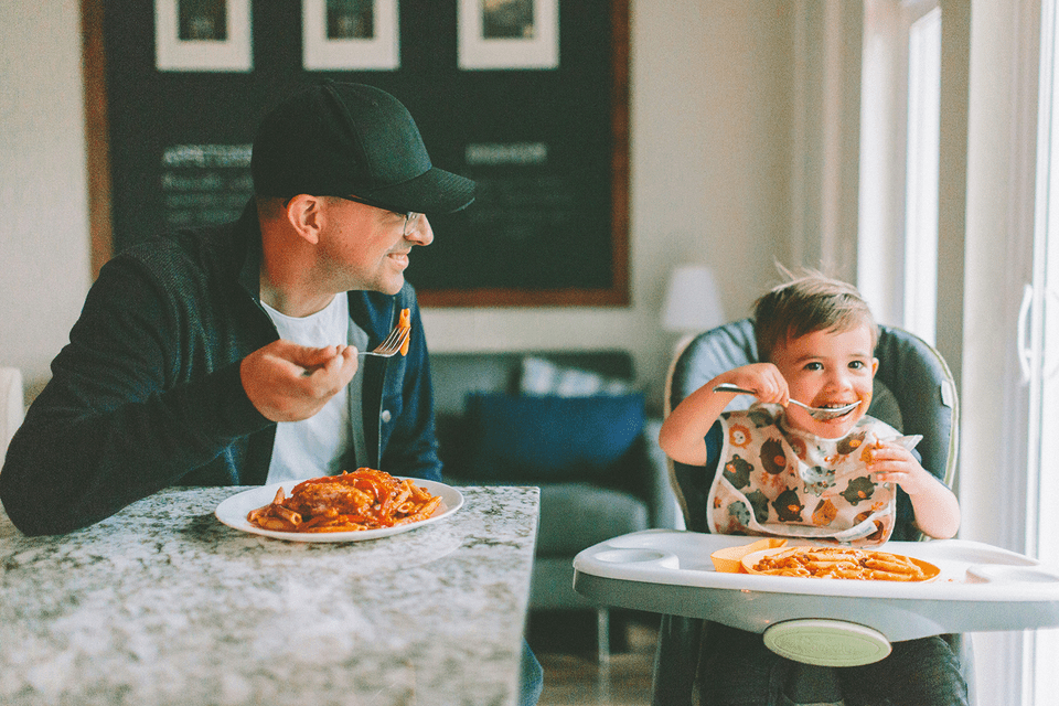 Father and Toddler Eating Pasta