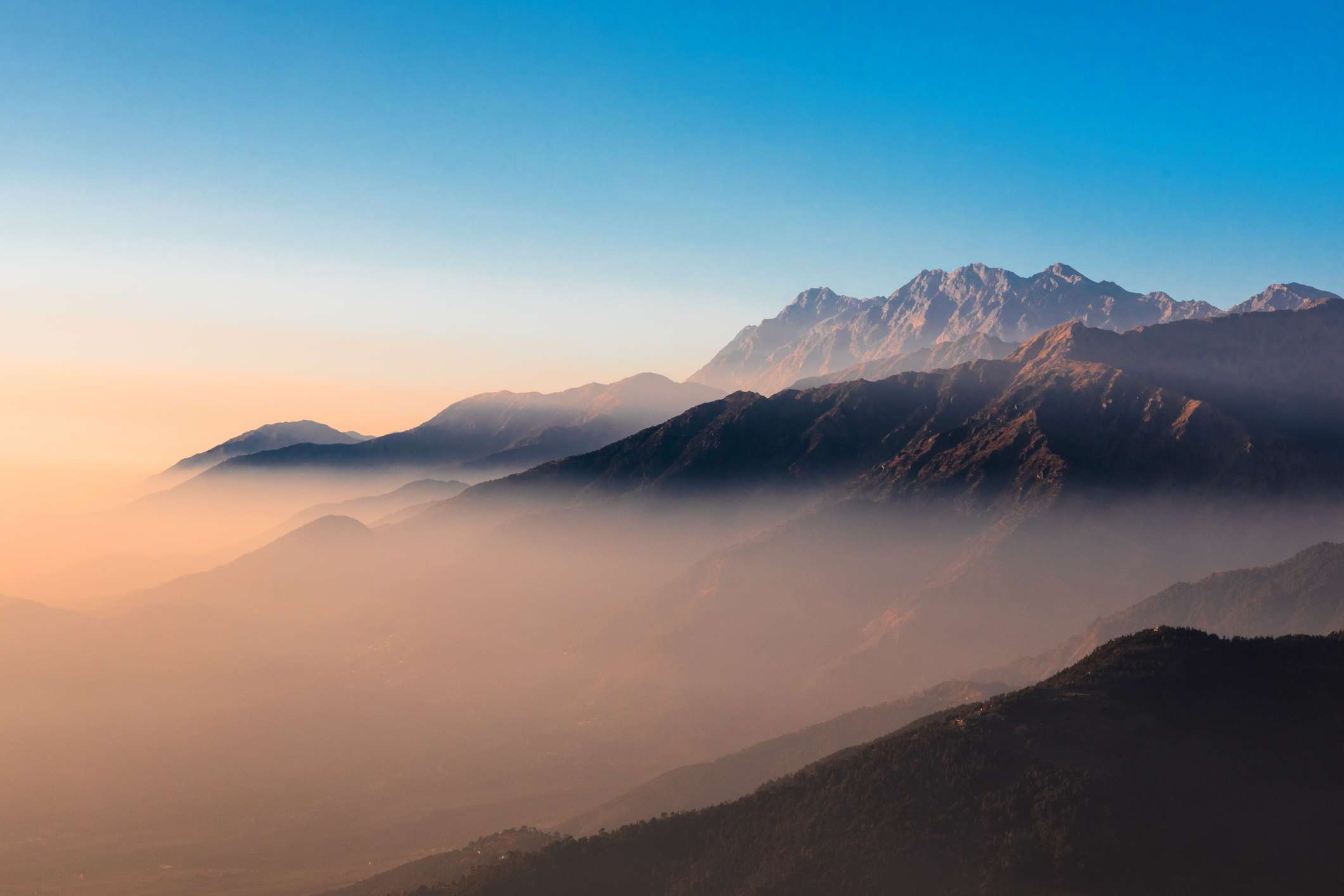 layered mountains with mist at sunrise