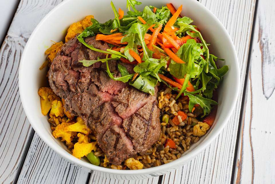 Rice bow with fresh greens, cauliflower, shredded carron and a cut-up steak on tope from Unleavened Fresh Kitchen