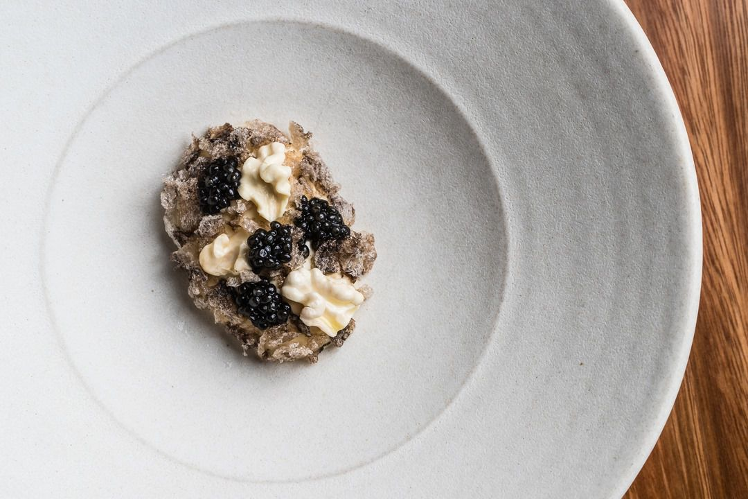 Osetra caviar, smoked eel, walnuts, sea cucumber crackling on a white plate