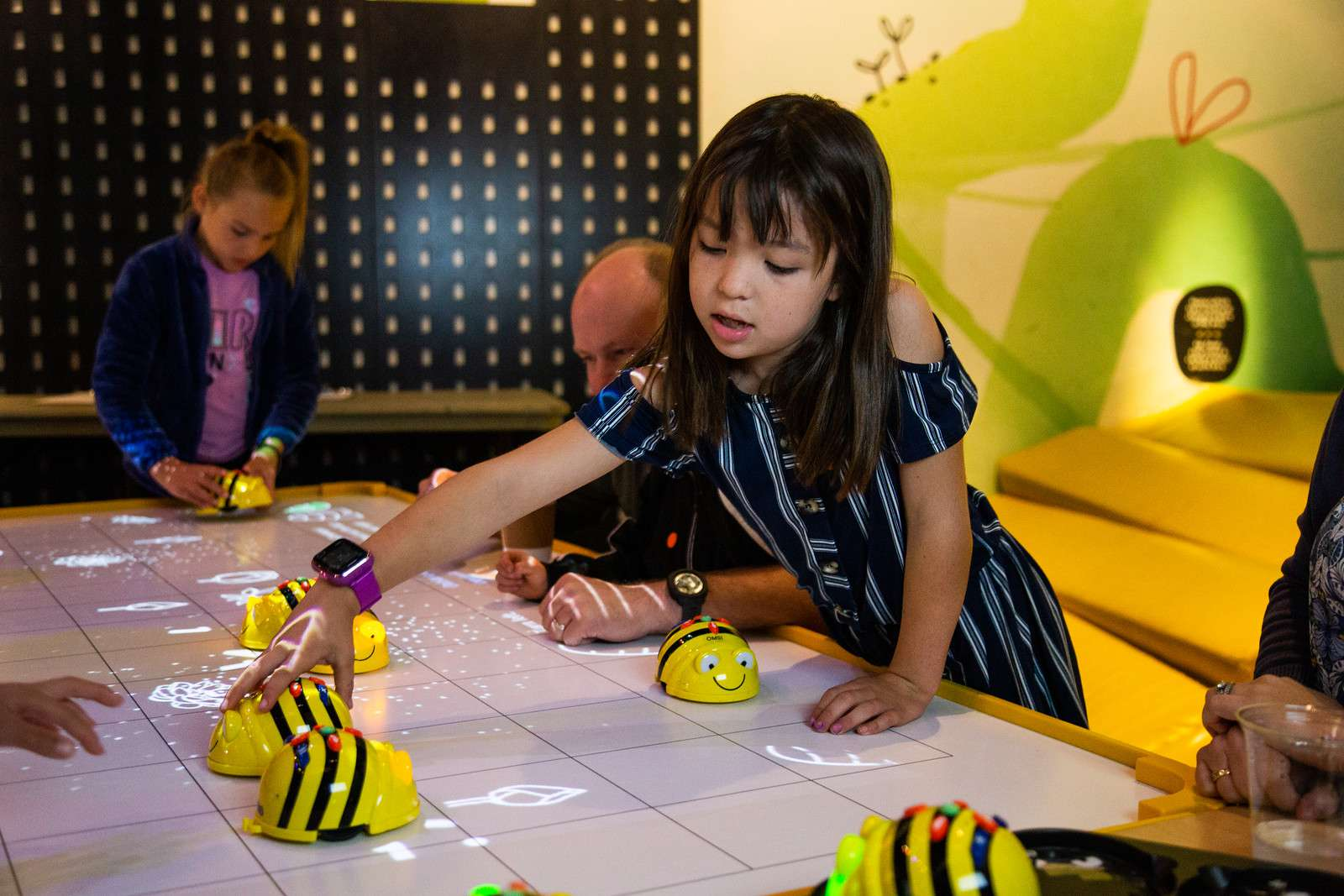 Little girl playing with bumble bee robot