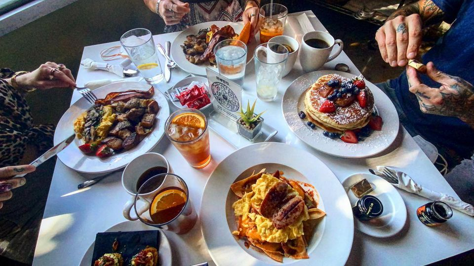 View of three people's torsos at a restaurant table with four breakfast entrees and many beverages