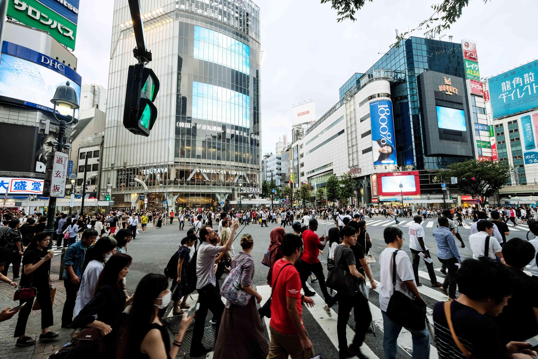 A large crowd of people crossing Shibuya Crossing