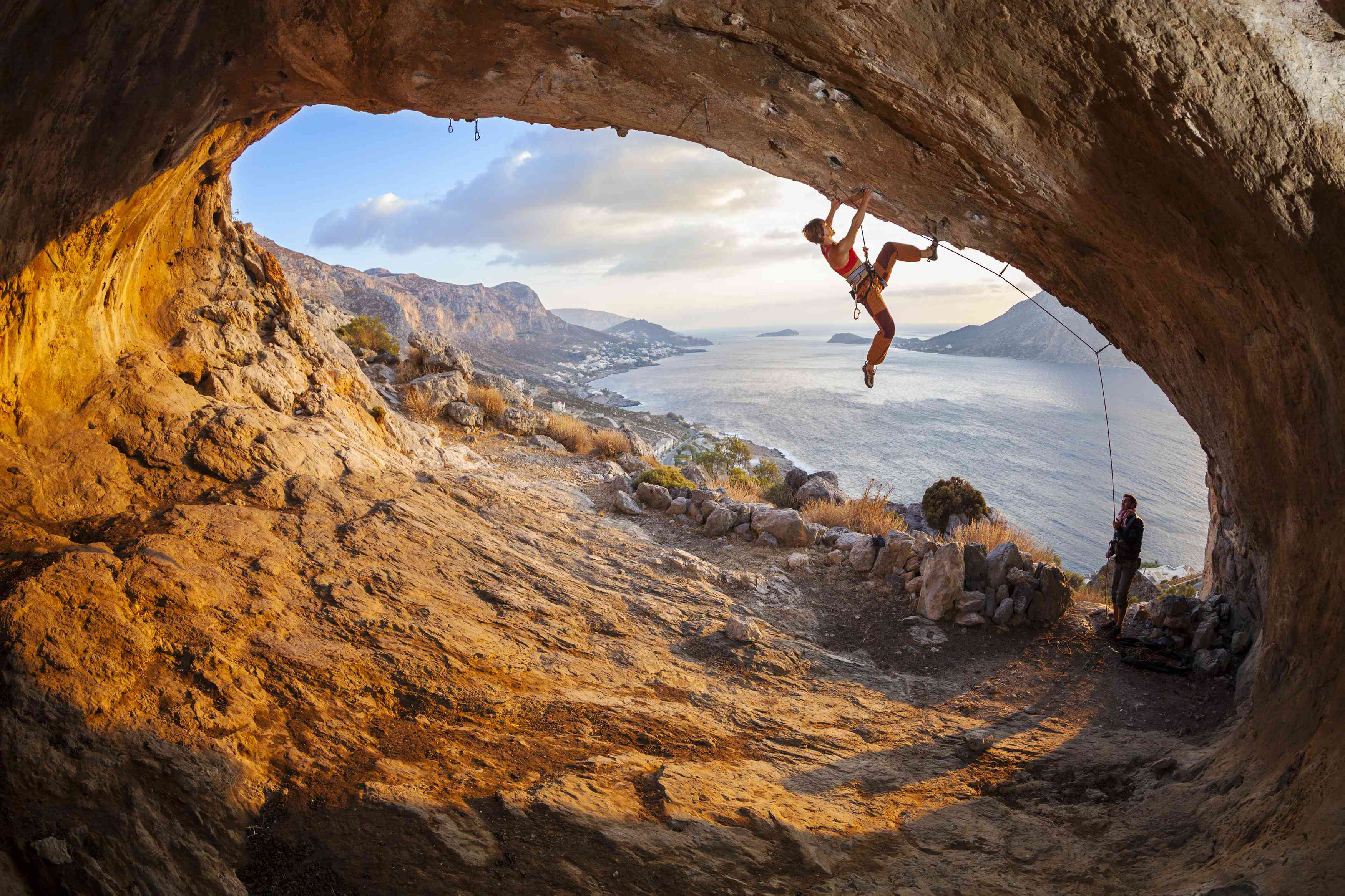 Young woman lead climbing in cave, male climber belaying. Kalymnos island, Greece.
