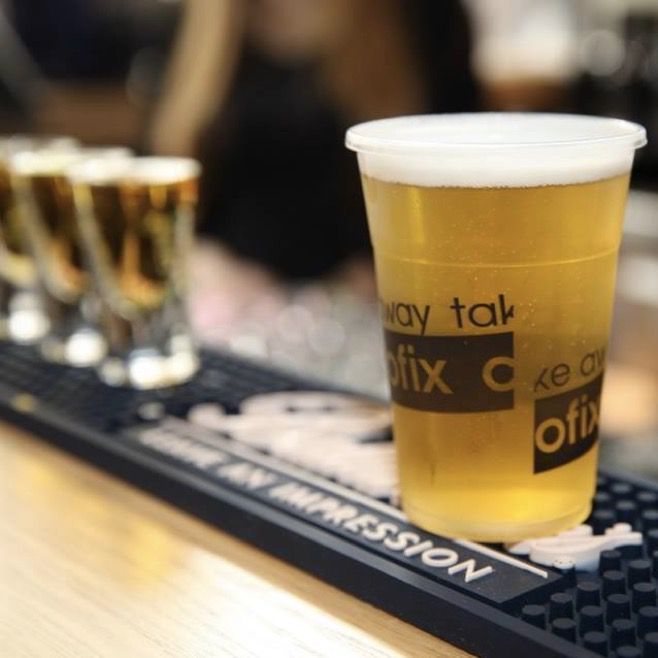 Clear plastic cup on a black, rubber mat filled with lite beer. There are two full shot glasses out of focus in the background