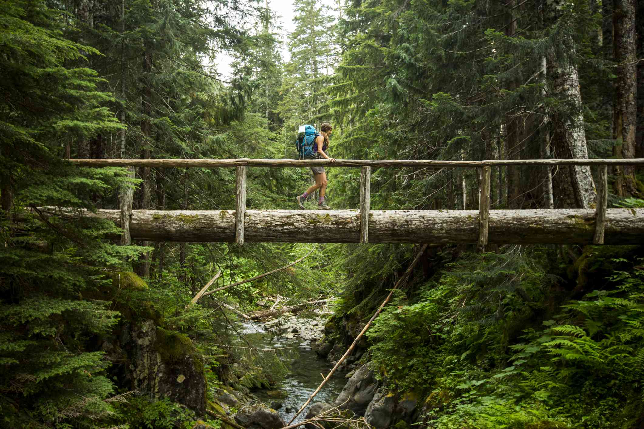 Woman crossing log bridge over a stream in Olympic National Park