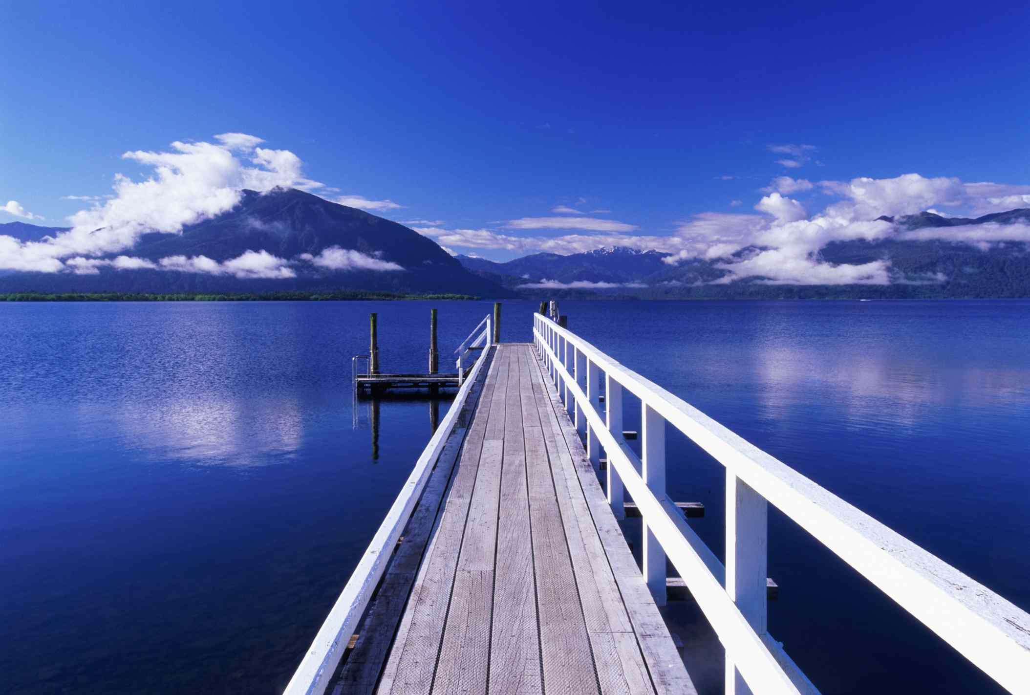 white wooden jetty leading into calm blue lake with mountains and wispy white clouds in background