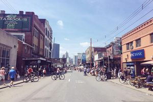 Bicyclists and pedestrians fill the street on a weekend in the Strip District.