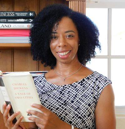 """Karen Rollins, a black woman with curly hair, smiling while holding a copy of """"A Tale of Two Cities""""."""