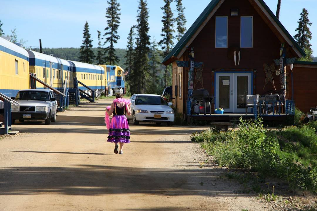 A guest walks back to her room in one of the train cars