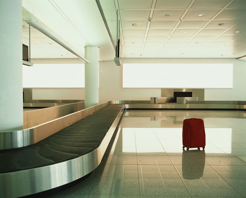 solitary suitcase adjacent to an empty luggage carousel