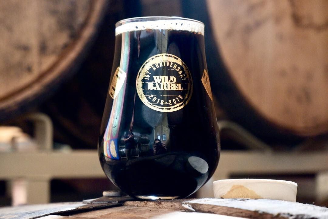 Dark beer in a stemless glass on a barrel