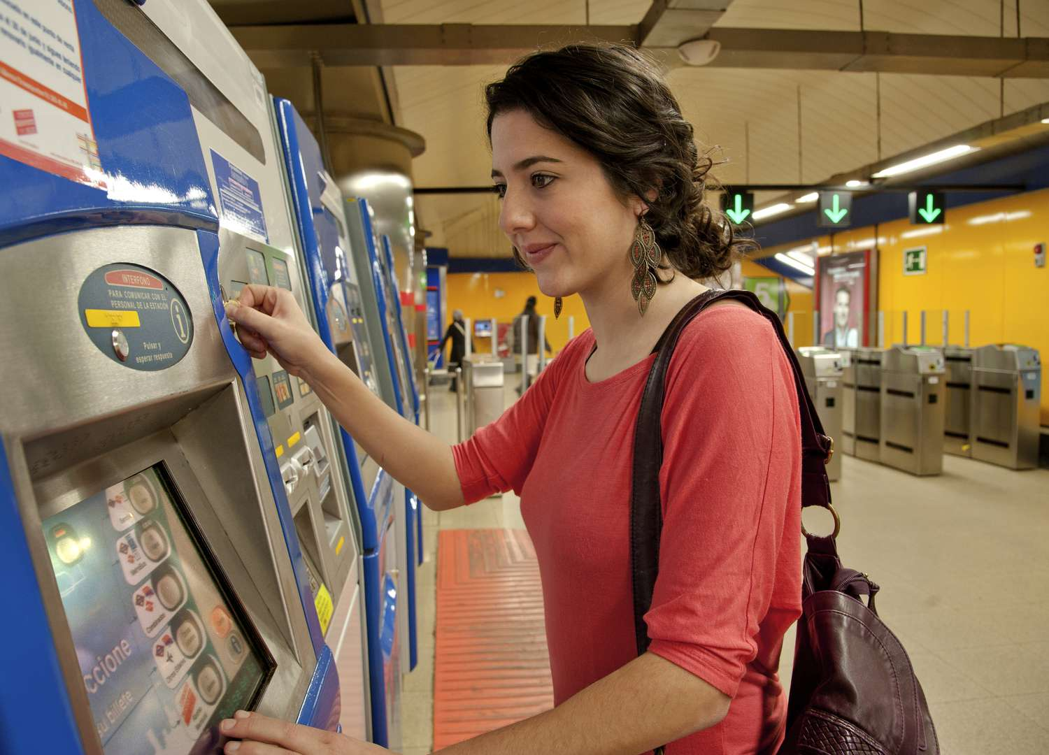 Woman purchasing tickets from an electronic machine at a metro station in Madrid