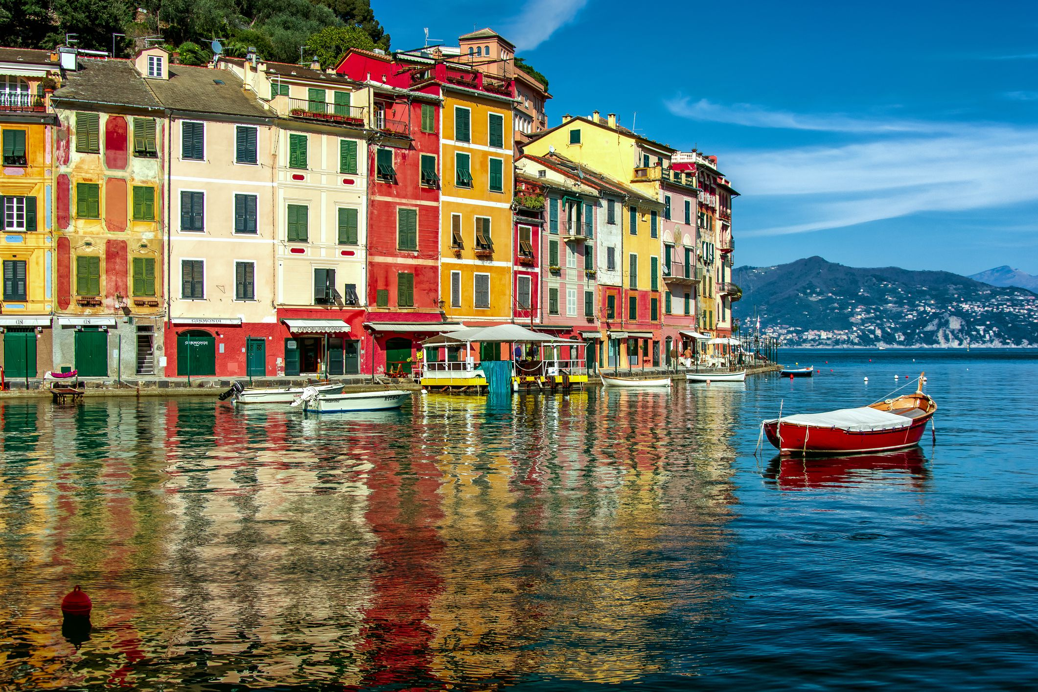 Multicolored waterfront houses and harbor with anchored motor boats in Portofino, Italy