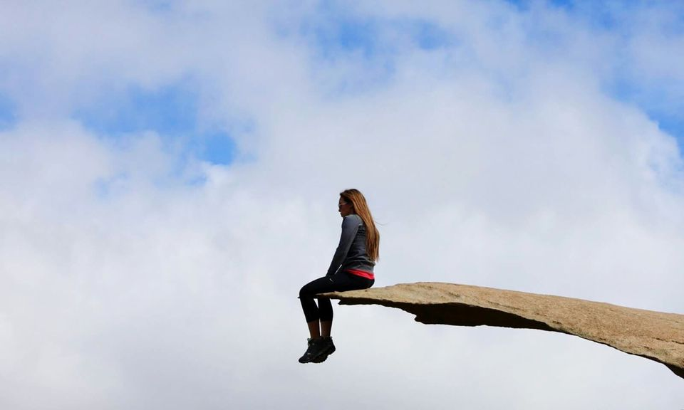 Low Angle View Of Woman Sitting At Potato Chip Rock Against Sky