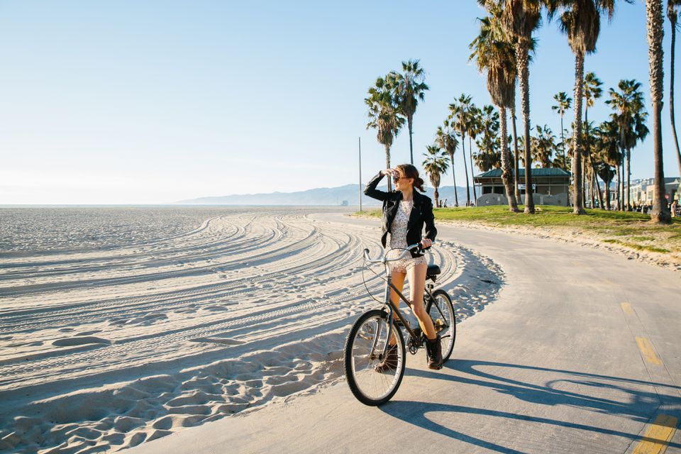 Young Woman Cycling At Beach Looking Out To Sea Venice California Usa