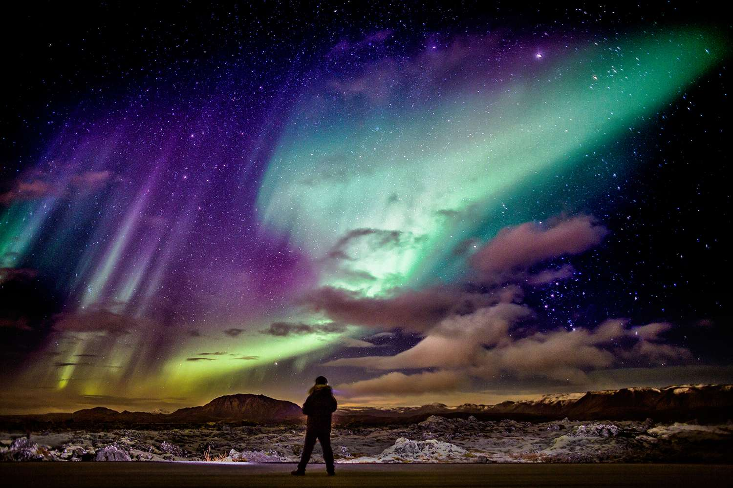 Person viewing the Northern lights over the lava landscape, Reykjanes Peninsula, Iceland.