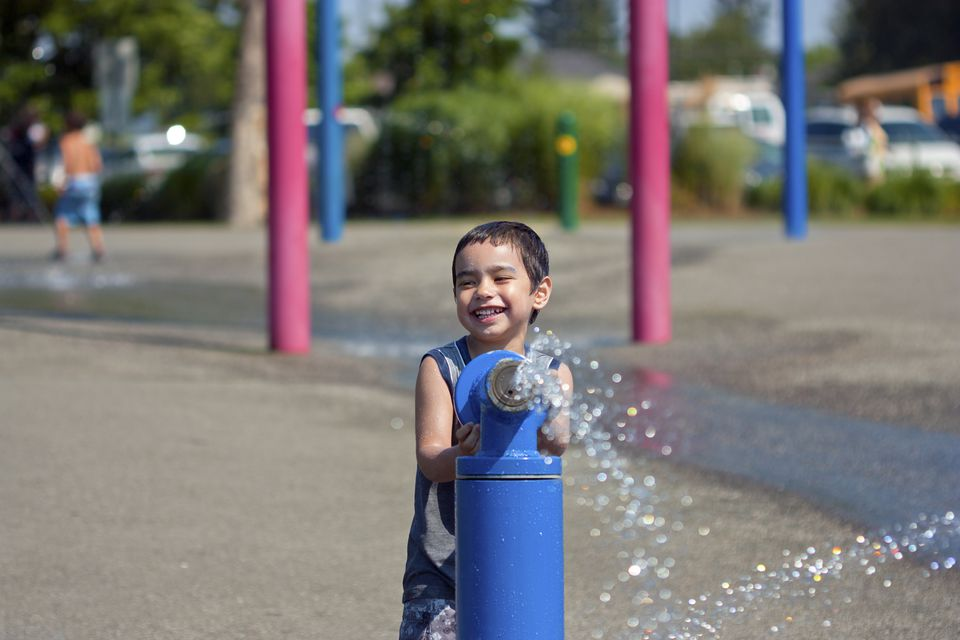 Happy boy spraying water at water park