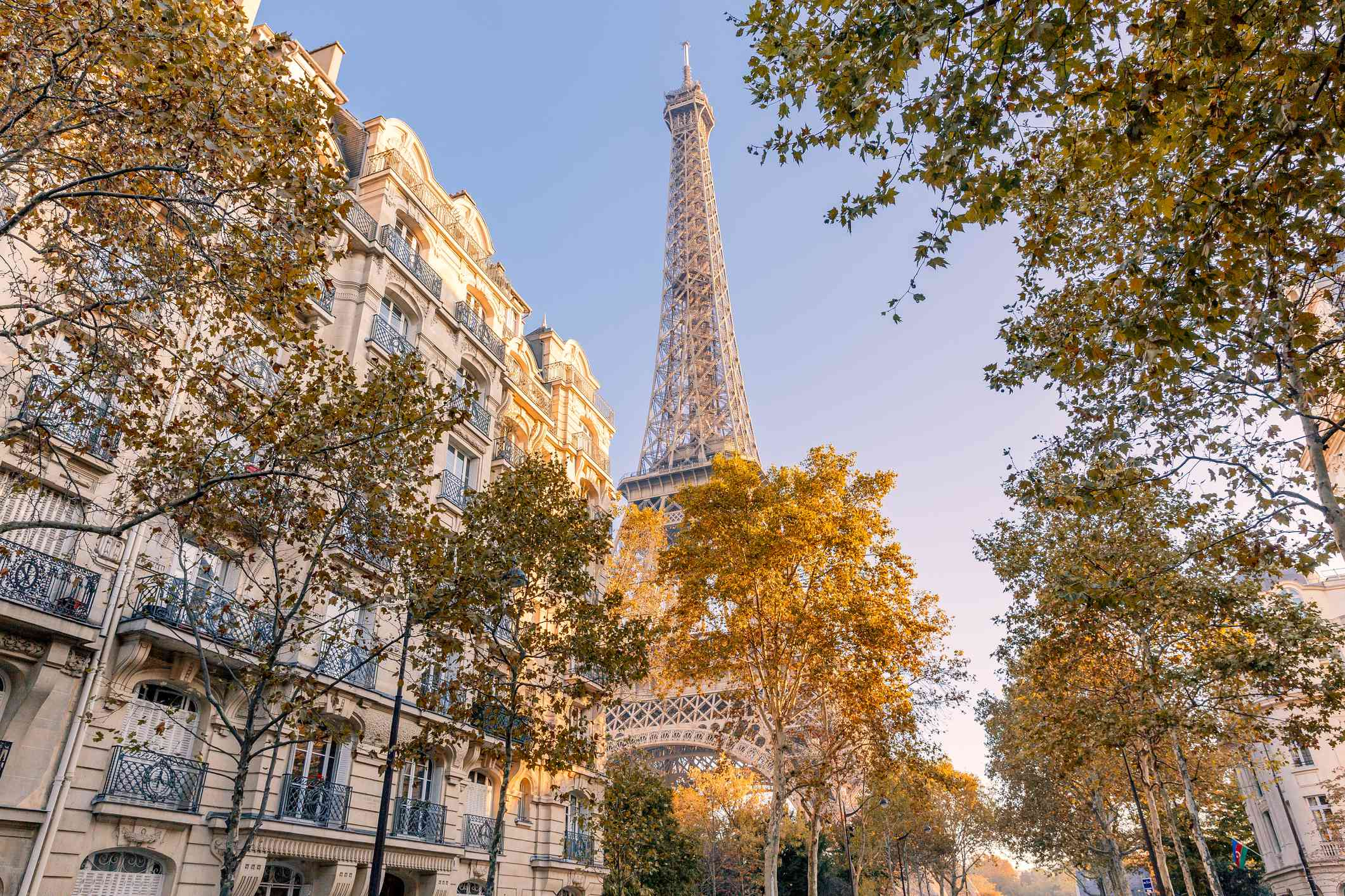 Low angle view of the Eiffel Tower in Autumn with buildings and trees in the foreground