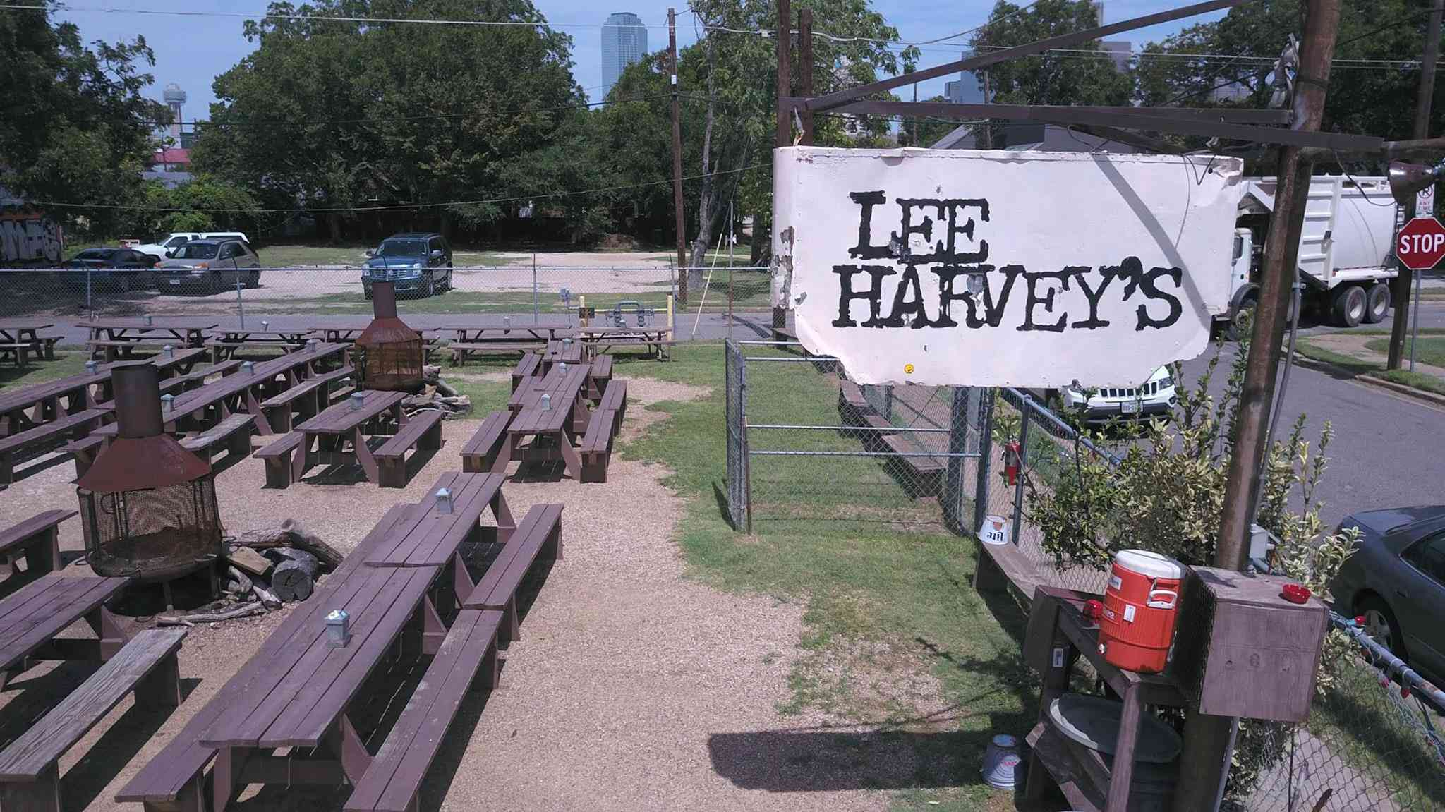 Outdoor wooden picnic tables in a gravel lot. There is a sign to the right of the tables that says