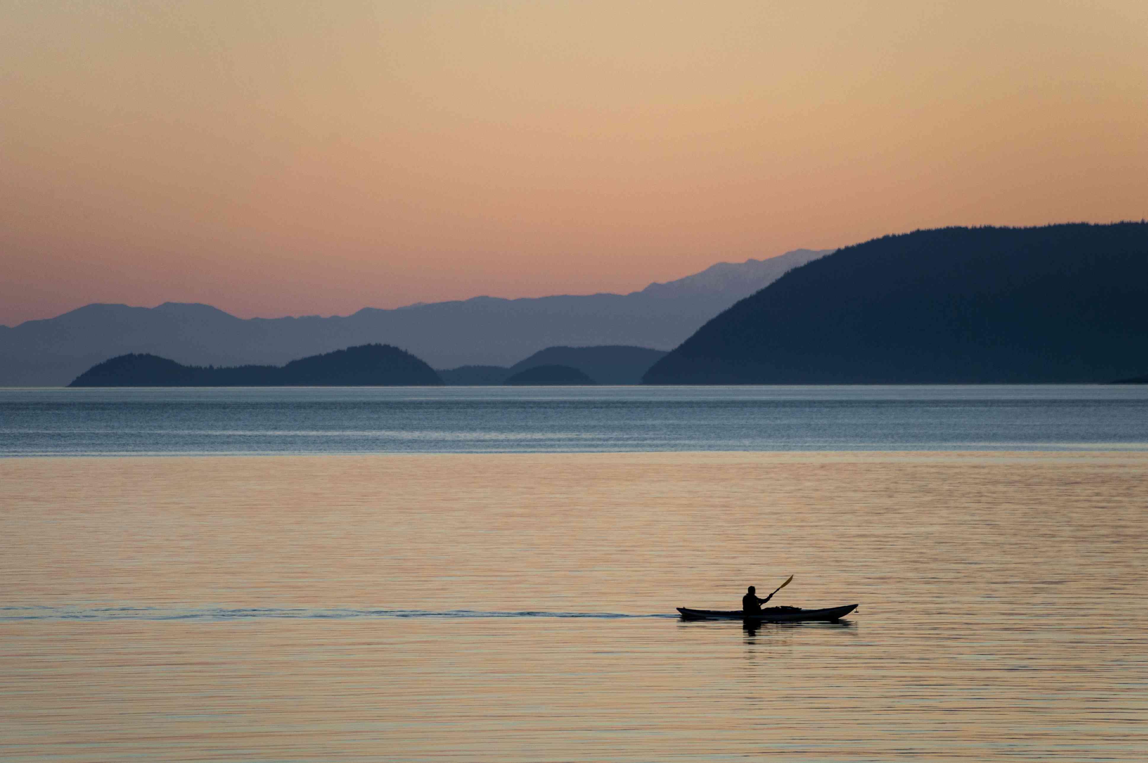Kayaking at Sunset Through the San Juan Islands of Washington State.