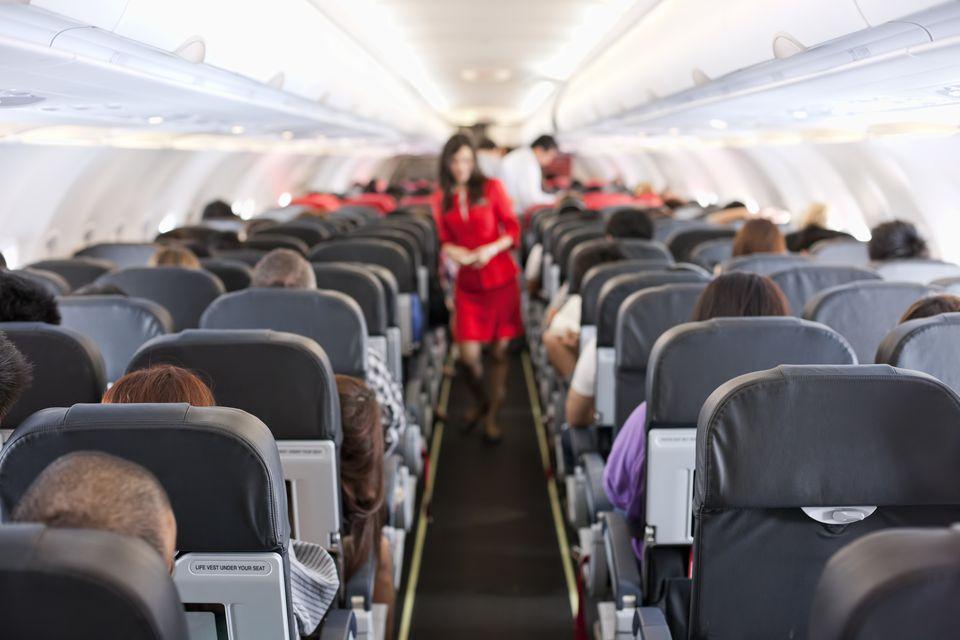 flight attendant walking up aisle of plane