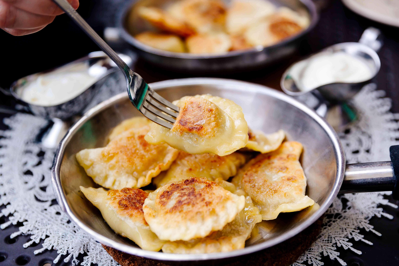 Comer albóndigas tradicionales polacas Pierogi con un tenedor