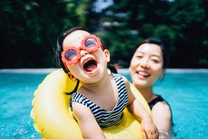 Happy toddler with sunglasses smiling joyfully and enjoying family bonding time with mother having fun in the swimming pool in summer