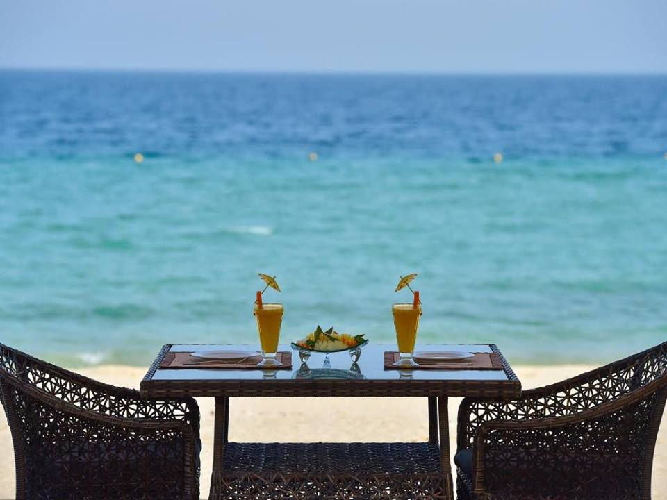 Two wicker chairs and a table with two orange-colored drinks and two place settings with a view of a beach and blue waters in the background